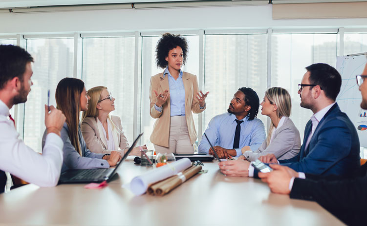 Woman speaks to team during meeting